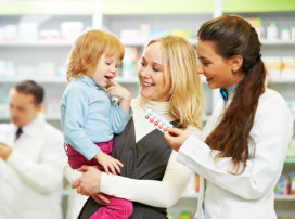 Pharmacist with a woman carrying her child