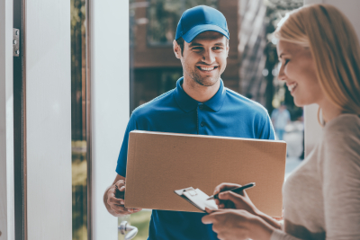 Delivery man and young girl signing to get her package
