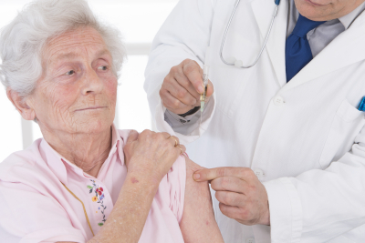 Doctor injecting vaccine to woman