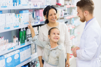 Young girl asking a pharmacist with her mother